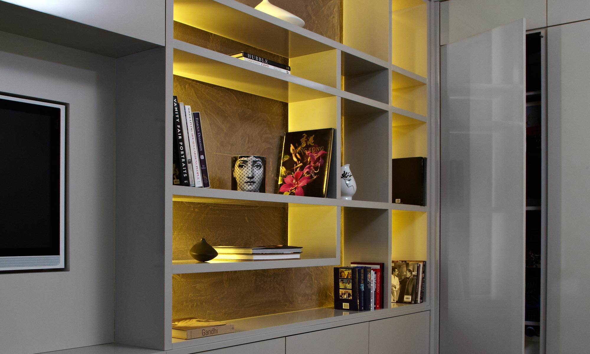 Grey gloss and gold, fitted storage unit with TV storage and recessed lighting in a London house