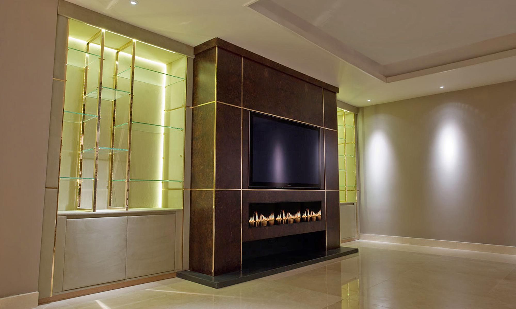 Walnut, glass and gold fitted bespoke media unit with feature fire