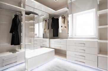 Beautiful white walk in wardrobe in white gloss and glass