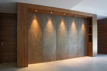 bespoke fitted storage unit made from walnut with downlighters